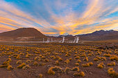 Sunrise in the Andes mountain range of Chile with the steaming water vapor of the Geysers in El Tatio Geyser Field (highest in the world), Atacama Desert, Chile, South America.