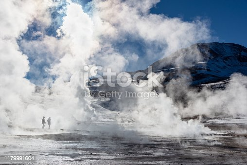 El Tatio geysers in Chile, Silhouettes of tourists among the steams and fumaroles at sunrise
