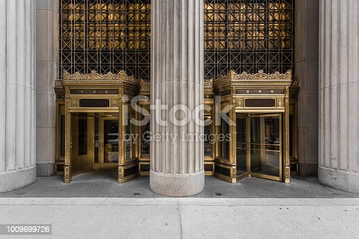 Elaborate golden revolving doors with giant column