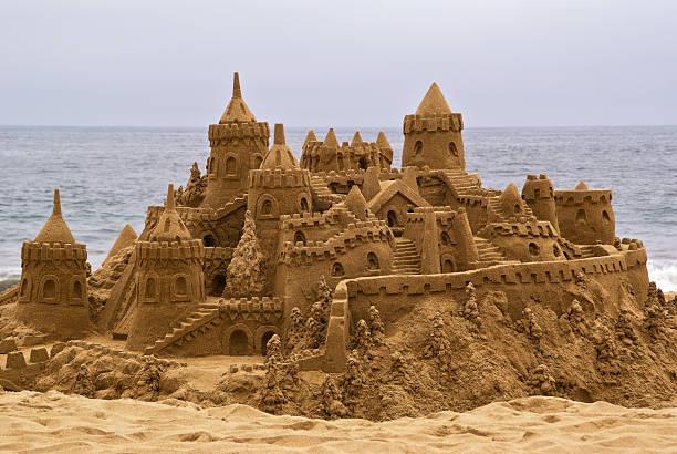 château de sable sur la plage, avec vue sur l'océan en toile de fond. - chateau de sable photos et images de collection