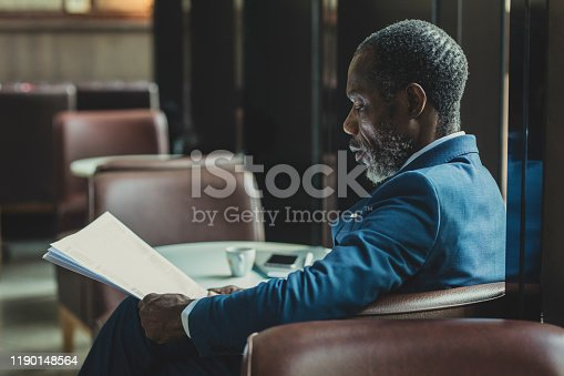African businessman wearing suit and tie sitting at coffee shop and reading daily newspaper.