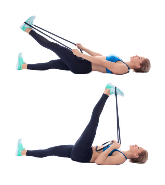 Elastic band hamstring stretch Elastic band exercises executed with a professional trainer. hamstring stock pictures, royalty-free photos & images