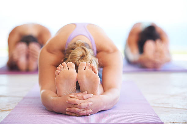 Elasti-Women! Yoga instructor leading a class in stretching touching toes stock pictures, royalty-free photos & images
