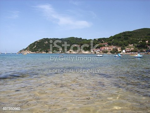 Portoferraio, Elba Island, Tuscany, Italy - July 22, 2009: The sandy beach of Scaglieri, located along the northern coast near Portoferraio, unusually invaded by seaweed from a recent storm