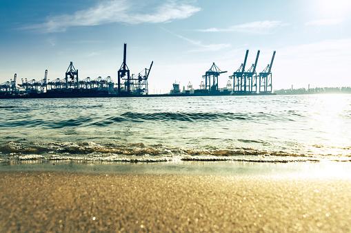 Elbe beach in Hamburg with Cargo cranes