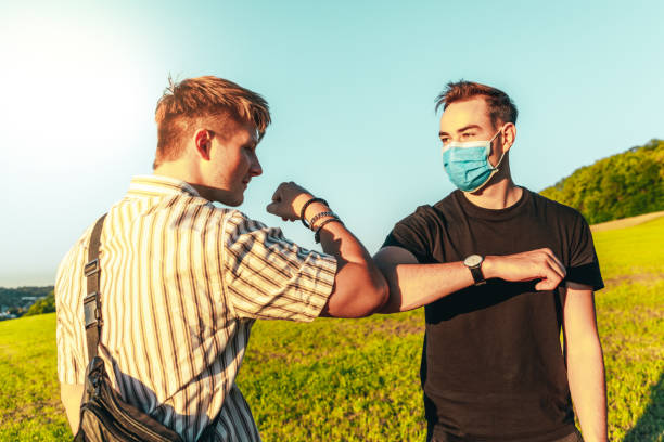 Elbow Bump Friends Greeting with Protective Face Masks stock photo