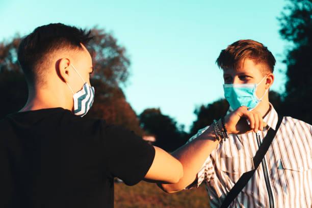 Elbow Bump Greeting Young Men with Face Masks Covid-19 Corona Virus stock photo