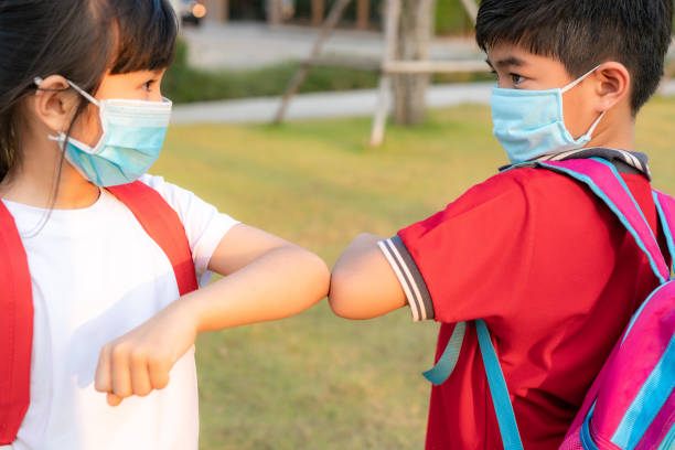 elbow bump is new novel greeting to avoid the spread of coronavirus. two asian children preschool friends meet in  school park with bare hands. instead of greeting with a hug or handshake, they bump elbows instead. - two students together asian foto e immagini stock