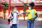 Two kids in a schoolyard during the coronavirus pandemic. Both about 10 years old, African female and Caucasian male.
