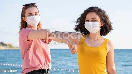 Elbow bumping. A new way of greeting to avoid the spread of coronavirus (COVID-19). Two people bump elbows instead of hug or handshake, Beautiful Girls Wearing Medical Masks During The Coronavirus COVID-19 Outbreak.