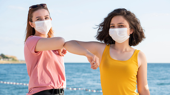 Elbow bumping. A new way of greeting to avoid the spread of coronavirus (COVID-19). Two people women bump elbows instead of hug or handshake, Beautiful Girls Wearing Medical Masks During The Coronavirus COVID-19 Outbreak.