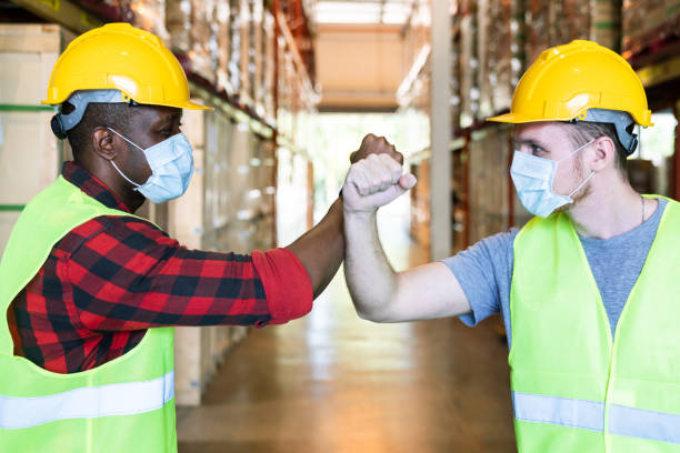 Elbow greeting to avoid the spread of coronavirus (COVID-19). African and caucasian worker man wear face mask greeting with elbow bump at warehouse. Employee avoid touch for coronavirus prevention. stock photo