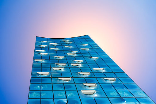 Elbphilharmonie, Close up shot - bright blue sky and bright sun light and flares from behind, Hamburg, Germany