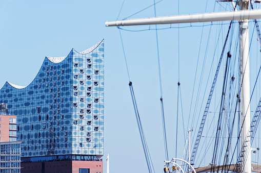 Elbphilharmonie - Elbe Philharmonic Hall in the harbor of Hamburg against clear blue sky and the mast of a sailing boot in the foregroung