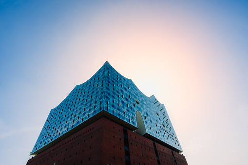 Elbphilharmonie with bright blue sky and sun light and sun flares over top shape of the building, Hamburg, Germany