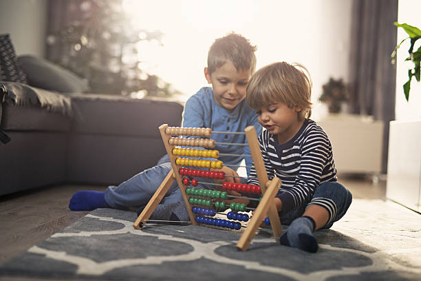 Elder brother helping little boy to count on abacus - foto stock