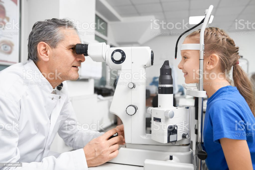Side view of process of checking eyesight in clinic. Elder doctor...