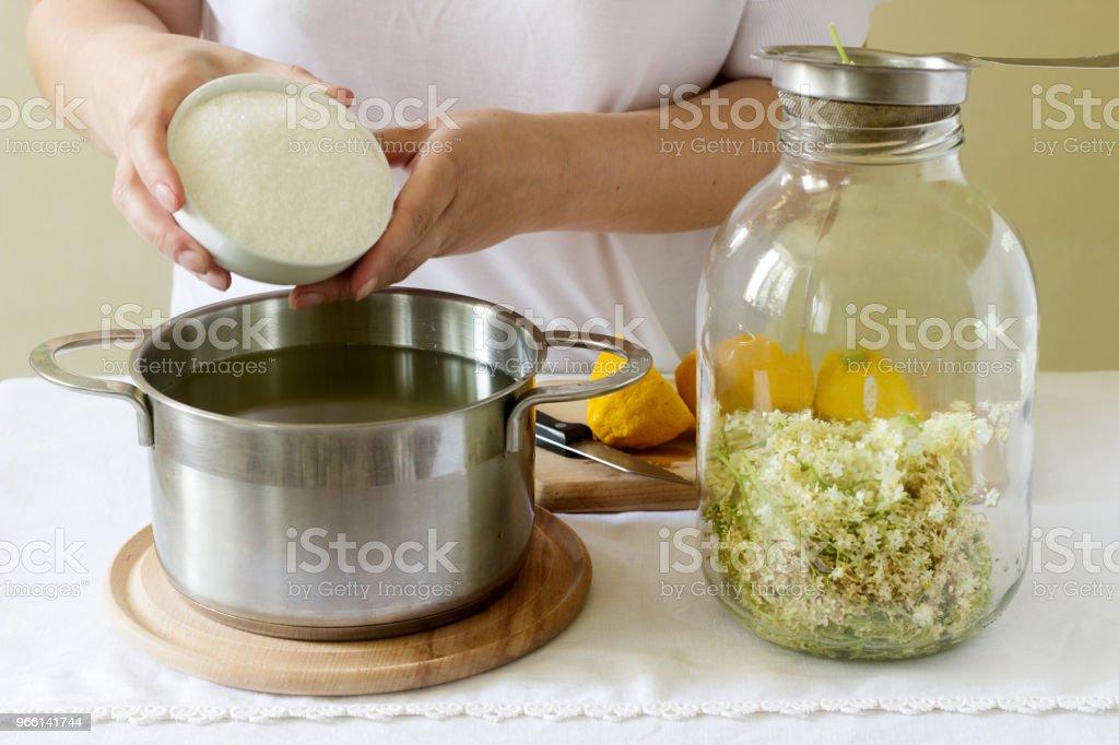 Fiori di sambuco, acqua, limone e zucchero, ingredienti e una donna che prepara uno sciroppo di sambuco. Stile rustico. - Foto stock royalty-free di Limone