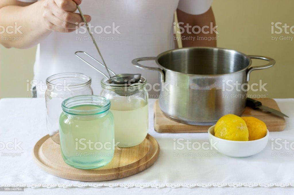 Fläder blommor, vatten, citron och socker, ingredienser och en kvinna som förbereder en fläderbär sirap. Rustik stil. - Royaltyfri Aromaterapi Bildbanksbilder