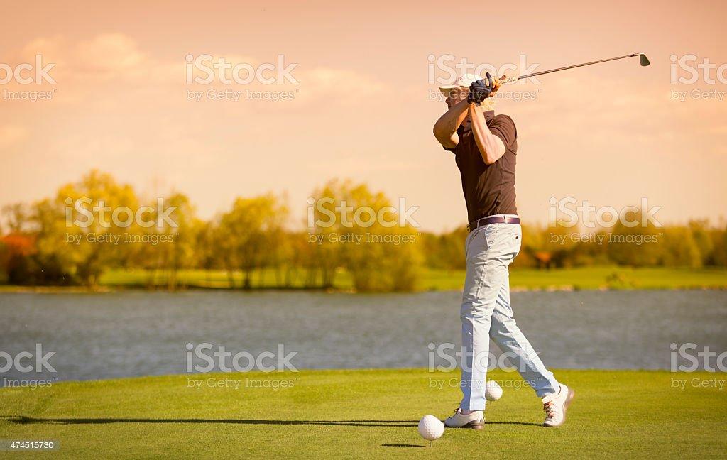 Elder golf player teeing off. stock photo