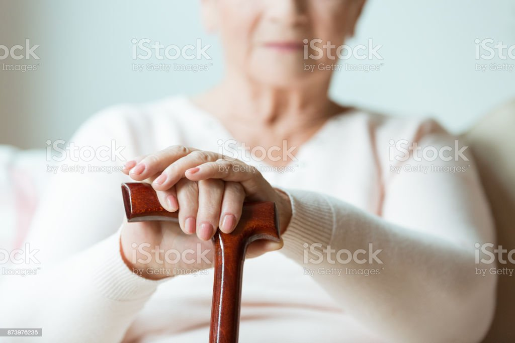 Elder holds hands on walking stick stock photo
