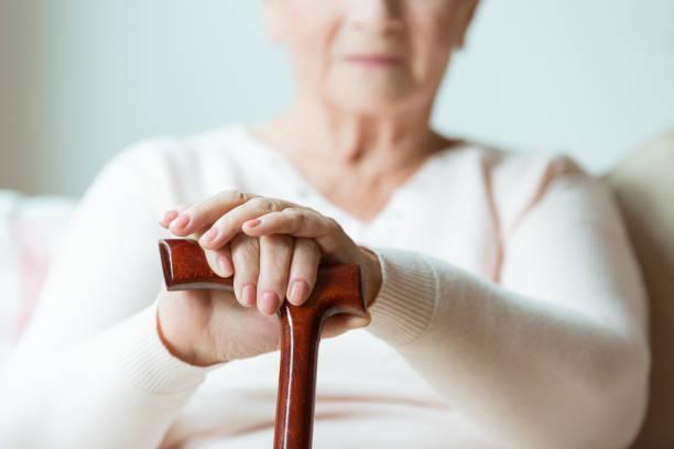 aîné détient les mains sur le bâton de marche - veuve photos et images de collection
