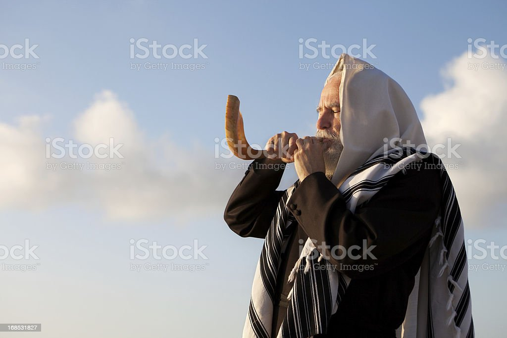 Elder Jewish man blowing a Shofar on Rosh Hashanah stock photo