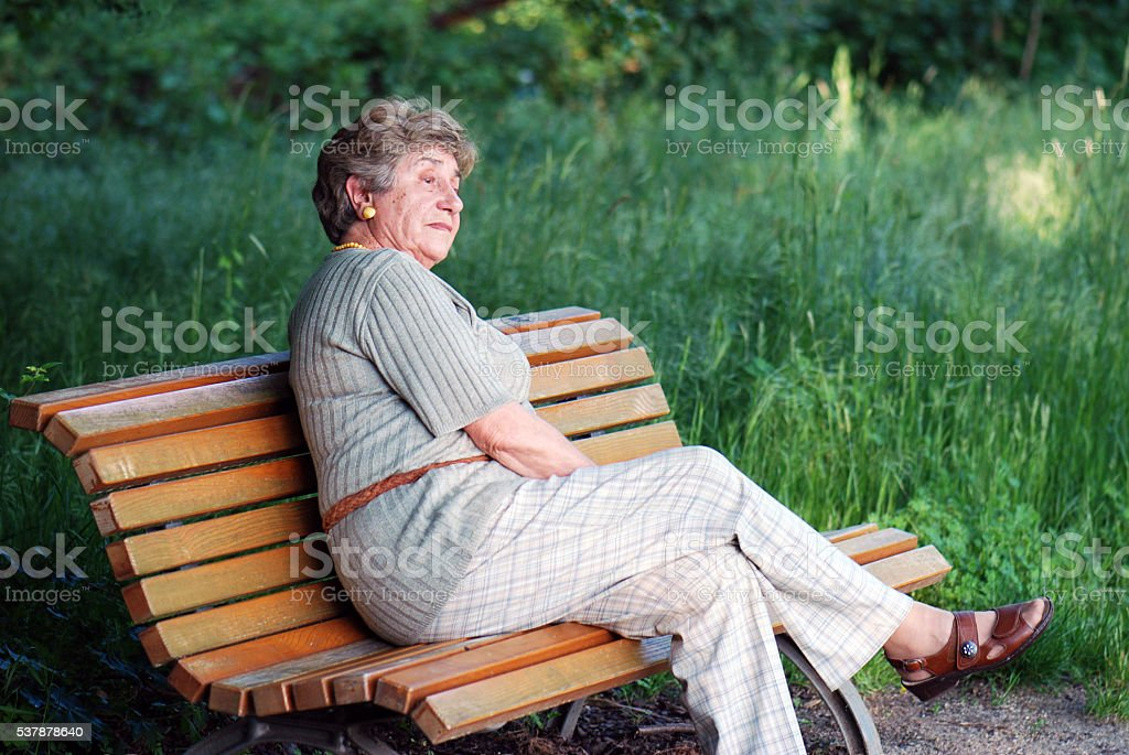 elder lady musing in the park stock photo