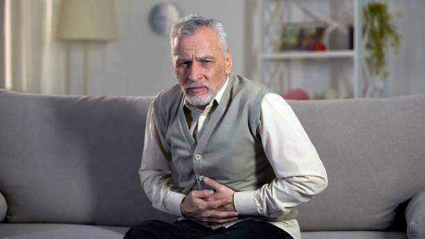 elder male suffering stomach ache, sharp cramps in upper abdomen, indigestion - ernia foto e immagini stock