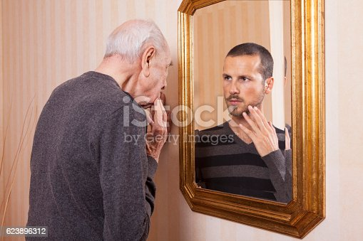 661896674istockphoto Elder man looking at an younger himself in the mirror 623896312
