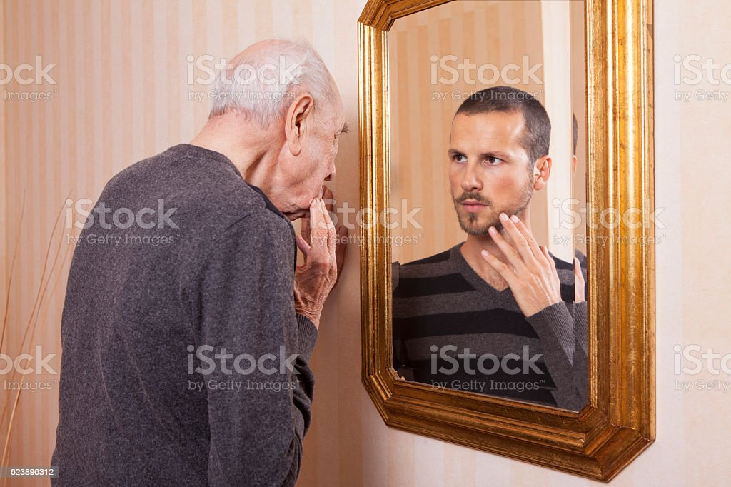 Elder man looking at an younger himself in the mirror stock photo