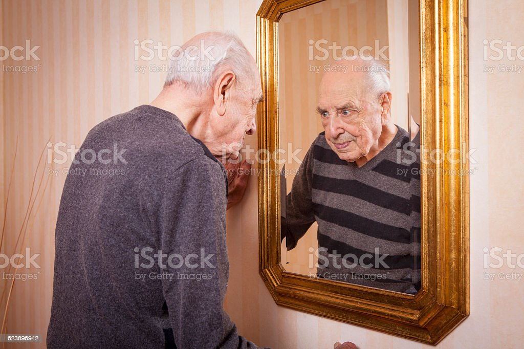 elder man looking at himself at the mirror stock photo