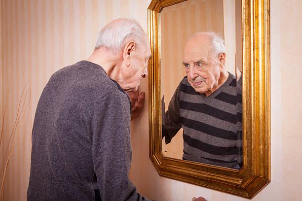 elder man looking at himself at the mirror - alte spiegel stock-fotos und bilder