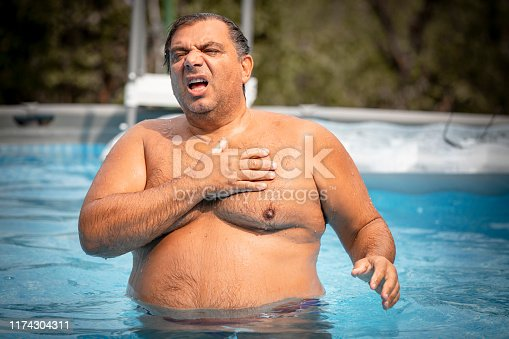 Heart attack concept. Mature man suffering from chest pain on Outdoor rain shower by swimming pool.