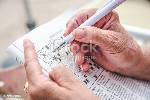 View of an old person completing a crossword puzzle.