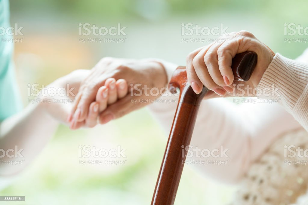 Elder person supported on stick stock photo