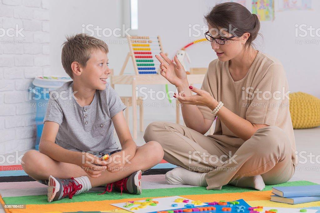 Elder sister teaching her brother stock photo