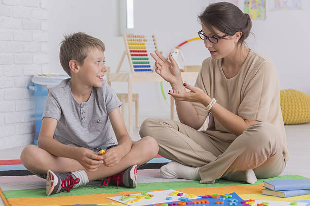 elder sister teaching her brother - school counselor stock photos and pictures