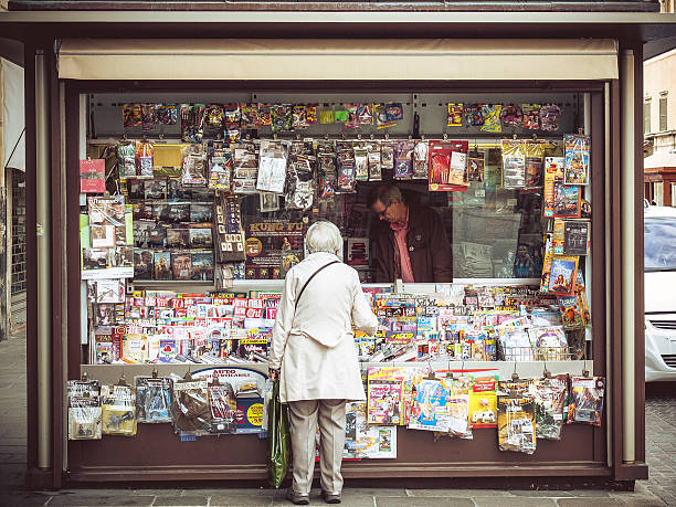 """Elder Woman Buying Magazine at Italian News Stand """"Ferrara, Italy- October 7, 2012: Elder Woman Buying newspapers at a news stand while the clerk is serving her."""" news stand stock pictures, royalty-free photos & images"""