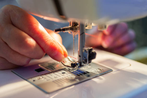 elder woman fingers inserting a red thread into a sewing machine's needle, close-up stock photo