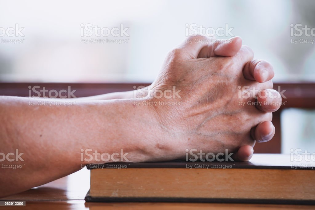 Elder Woman Hands Folded In Prayer On A Holy Bible Stock