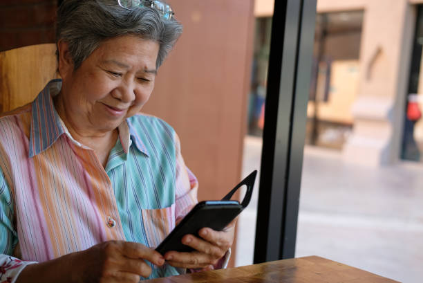 ältere Frau mit Handy im Garten. ältere Frauen SMS Nachricht, app mit Smartphone zu Hause verwenden. Senior Nutzung Handy Verbindung mit sozialen Netzwerken – Foto