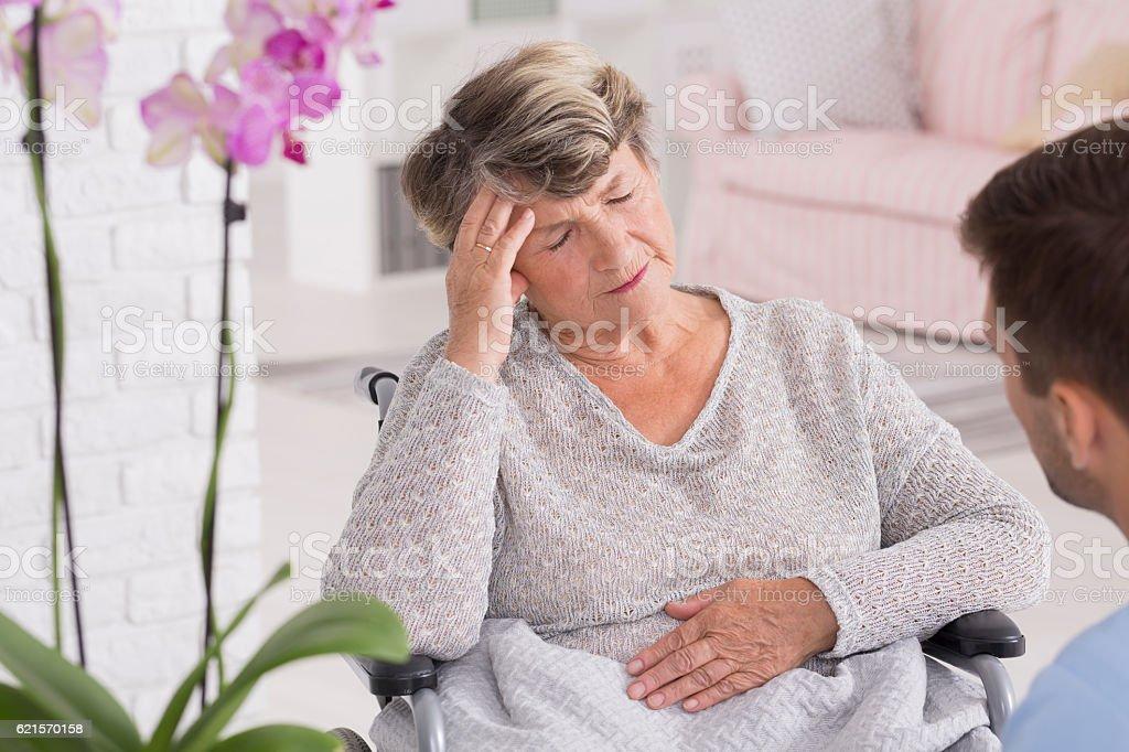 Elder woman on a wheelchair with headache photo libre de droits