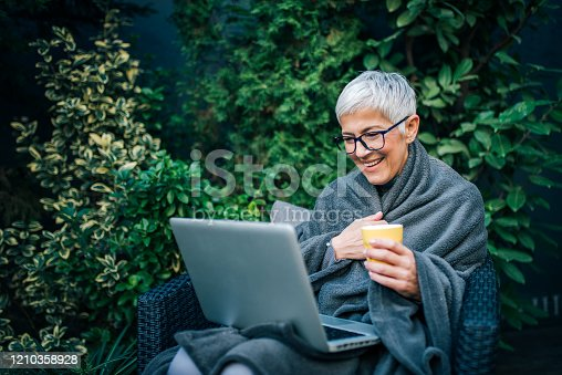 Elder woman sitting on a chair in backyard garden and looking at laptop, portrait.
