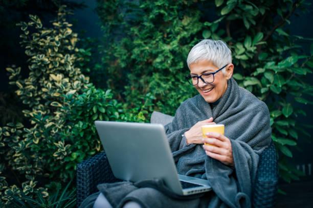 Mujer mayor sentada en una silla en el jardín del patio trasero y mirando la computadora portátil, retrato. - foto de stock