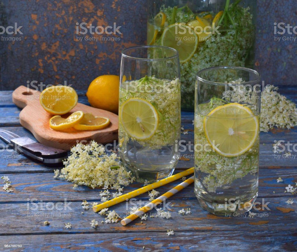 Elderberry flowers and lemon drink. Refreshing healthy summer juice. Glass of elderflower lemonade on wooden rustic board. Alternative medicine and therapy. royalty-free stock photo