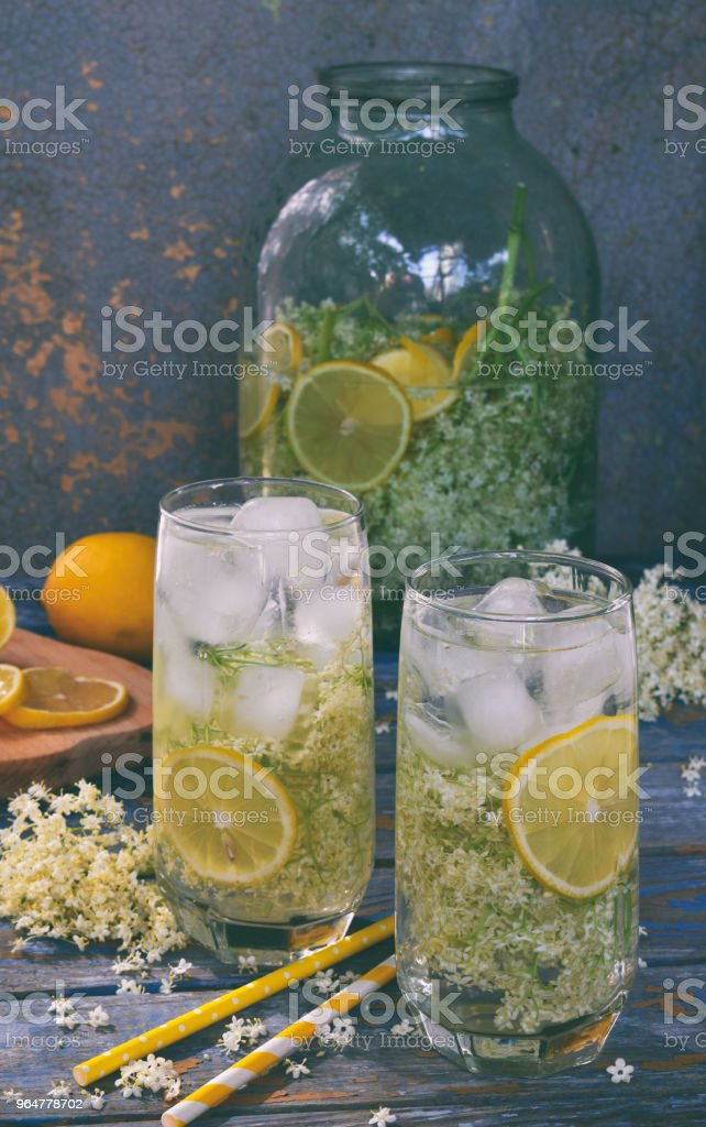 Elderberry flowers and lemon drink. Refreshing healthy summer juice. Glass of elderflower lemonade on wooden rustic board. Alternative medicine and therapy. royalty-free stock photo