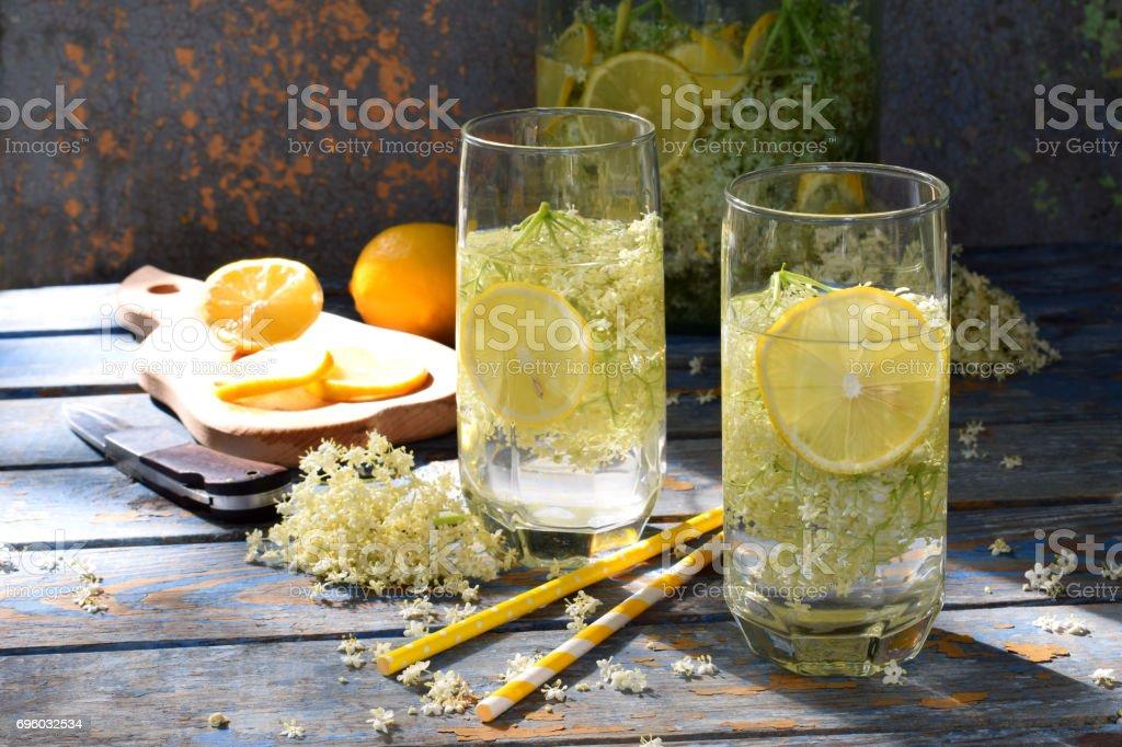 Elderberry flowers and lemon drink. Refreshment healthy elder juice. Glass of elderflower lemonade on wooden rustic board. Alternative medicine and therapy stock photo