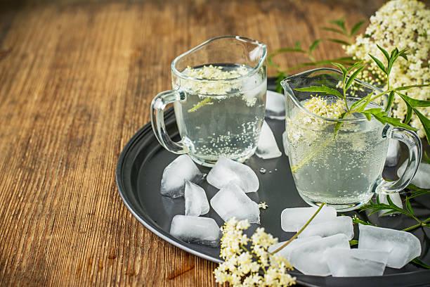 holundertee-drink mit holunderbeere blumen - holunderlikör stock-fotos und bilder