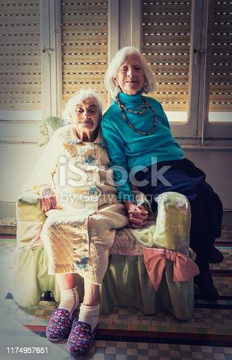 Elderly 90s real sisters portrait sitting in armchair at vintage living room